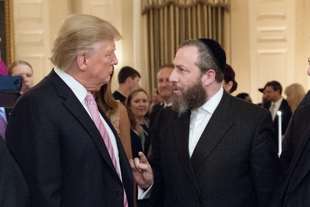 عزرا فريدلاندر، يهودي أرثوذكسي وصاحب شركة ضغط سياسي يعمل لصالح رجل الأعمال القطري حسان علي بن علي، ويظهر في الصورة مع الرئيس الأمريكي دونالد ترامب.