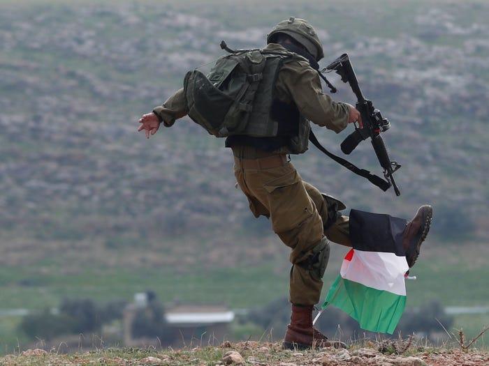 جندي إسرائيلي يركل علم فلسطين