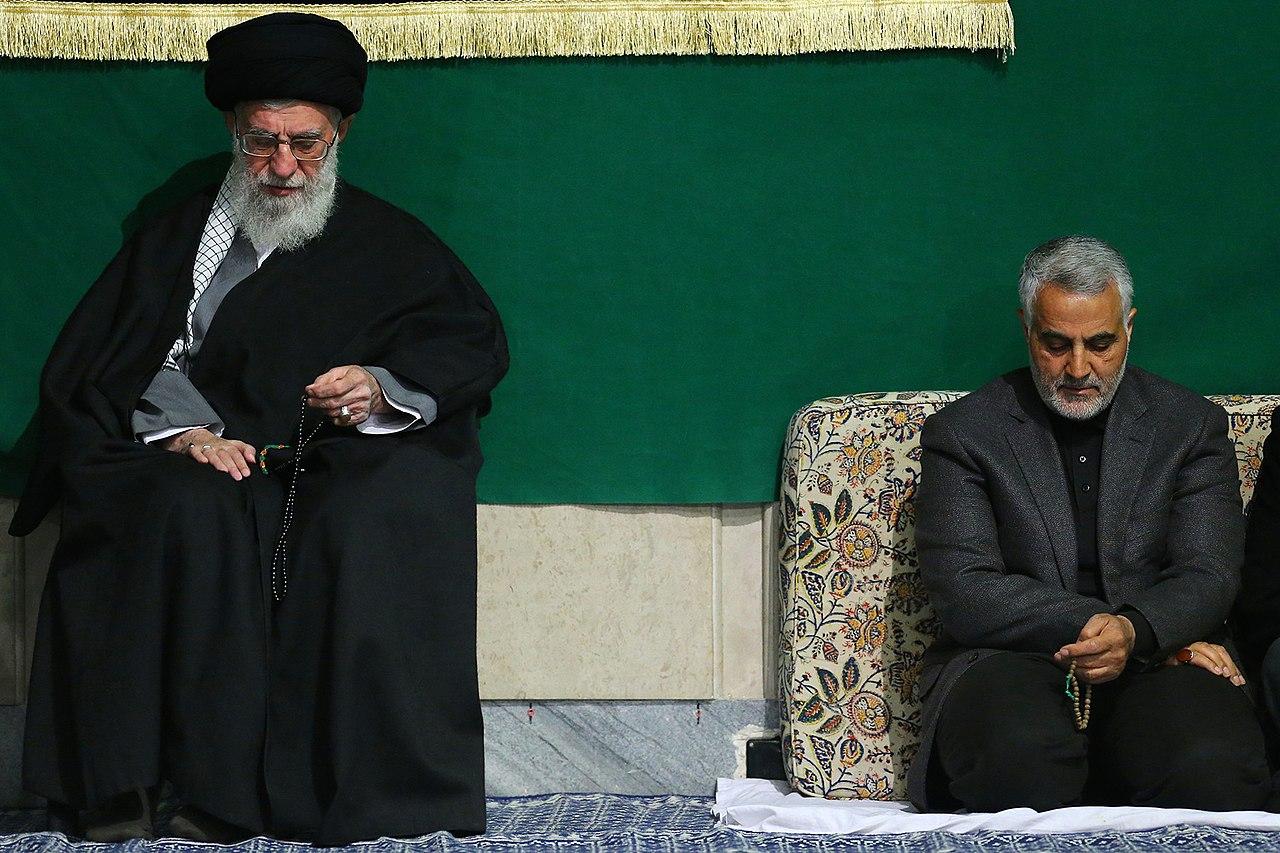 قاسم سليماني، قائد فيلق القدس في الحرس الثوري الإيراني، يجلس بجانب المرشد الأعلى لجمهورية إيران الإسلامية، علي خامنئي. مصدر الصورة: ويكي.